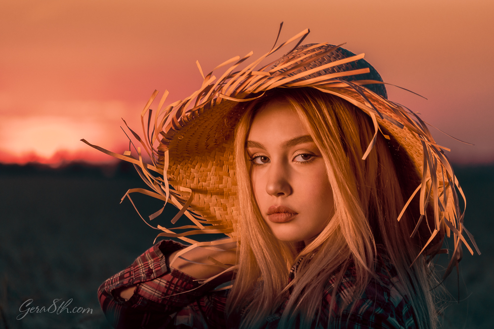 portrait of a young girl with blond hair in a straw hat in the evening at sunset in summer close up